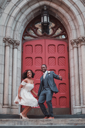 NEW YORK CITY, USA - July 10, 2018: african american just married couple outside the church jumping