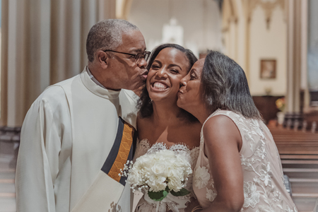 NEW YORK CITY, USA - July 10, 2018: priest kisses the bride at wedding in the church