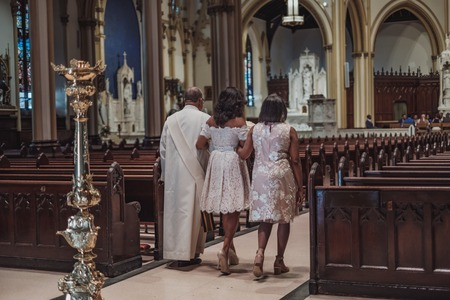 NEW YORK CITY, USA - July 10, 2018: bride with her family going to ceremony in catholic church