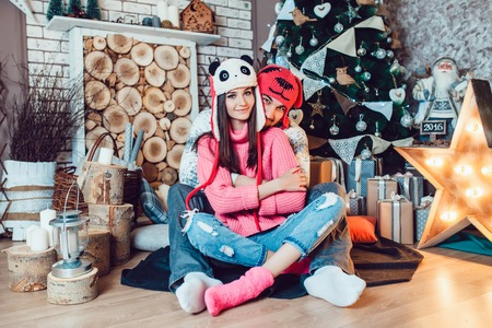 guy portrait: A  beautiful loving couple in funny hats posing in Christmas decorations