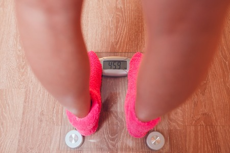 weigher: The girl in pink socks standing on weigher. Wood floor