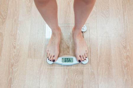 weigher: The girl standing on weigher. Wood floor