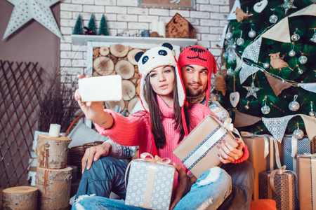 hacer el amor: Beautiful couple in love in Christmas decorations make the selfie
