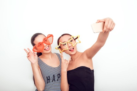 young  brunette: Asian girls in the funny sunglasses. They pose, grimace and look at the camera. Hair removed. The skin is clean. They make a picture on the phone.