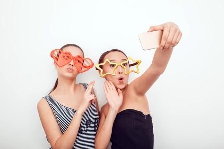 jolie fille: Filles asiatiques dans les lunettes de soleil dr�les. Ils posent, grimace et regardent la cam�ra. Retir� cheveux. La peau est propre. Ils font une image sur le t�l�phone.