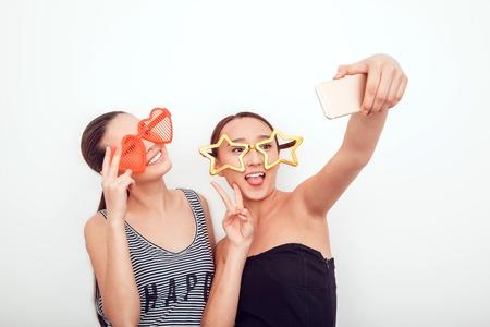 jovenes felices: ni�as asi�ticas en las gafas de sol divertidas. Plantean, mueca y mire a la c�mara. elimina el pelo. La piel est� limpia. Ellos hacen una foto en el tel�fono. Foto de archivo