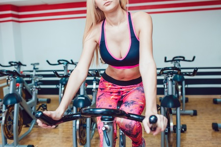 stationary bike: Young blonde woman on a stationary bike. Bright leggings. Stock Photo