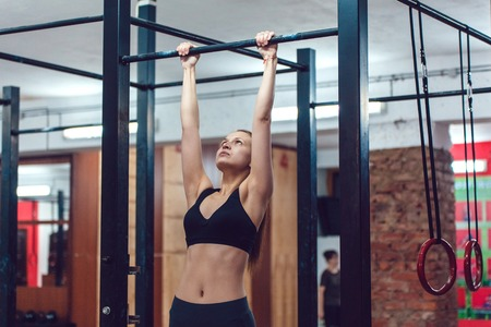 gripping bars: Sporty Girl does exercise on a horizontal bar