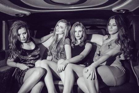 Sexy girls. Party in the car. Black and white Stock Photo
