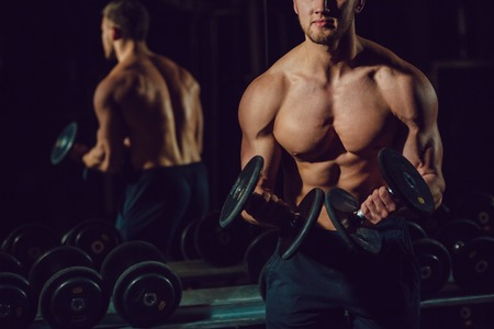 musculation: Very power athletic guy bodybuilder , execute exercise with dumbbells Stock Photo