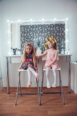 hair curlers: Little girl in hair curlers in a beauty studio