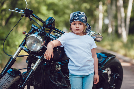 Little girl in a white T-shirt and bandana standing near a motorcycle Stock Photo