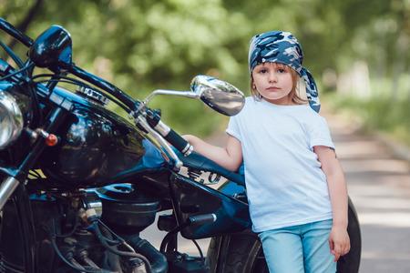 bandana girl: Little girl in a white T-shirt and bandana standing near a motorcycle Stock Photo