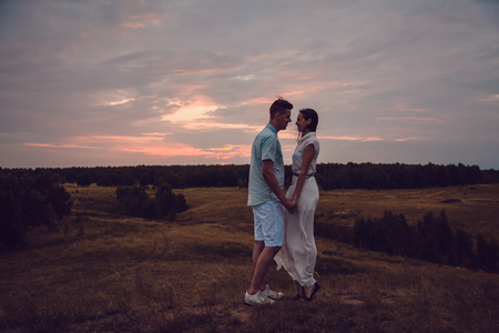 a meeting with a view to marriage: Love story. In love couple walking on sunset background. Happy end. Silhouette figures of people in love on the nature. Screensaver for the film.