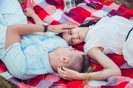 a meeting with a view to marriage: Beautiful young happy loving couple on picnic lying down on plaid on sunny summer day enjoying and resting. hugging and looking at each other and smiling.