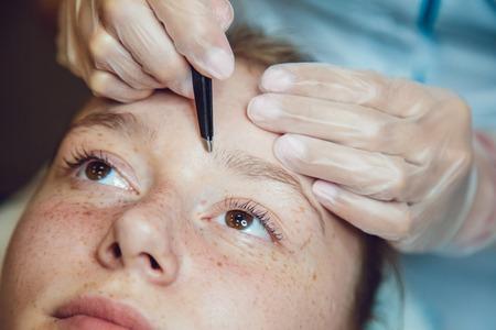 pinzas: El flujo de trabajo en una niña de salón de belleza cejas depiladas. Pinzas. Foto de archivo