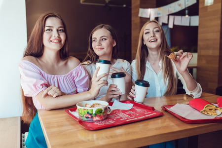 misbehave: Three cheerful young girls eating fast food in a restaurant