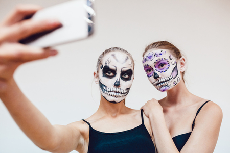 Two girls going on Halloween, grimace and make selfie Stock Photo