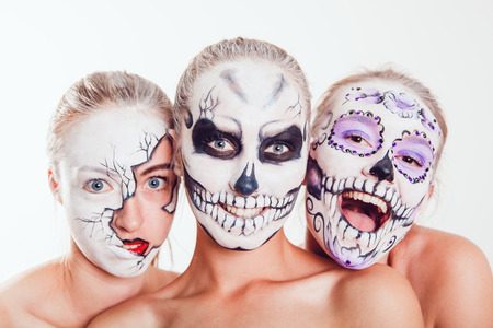 Three girls with Halloween face art on white background Stock Photo