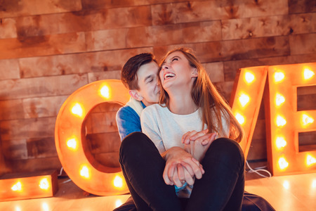 Young couple in love sitting on floor embracing Stock Photo