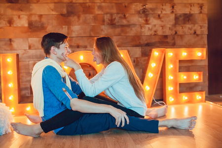 facing each other: Young couple sitting at home on the floor facing each other Stock Photo