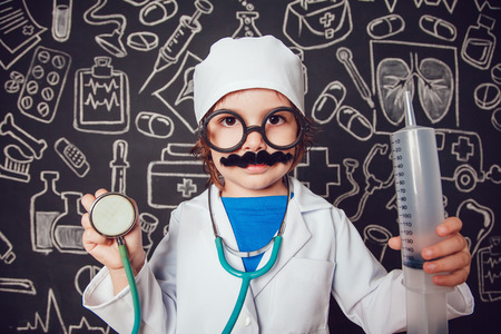 Happy little boy in doctor costum holding syringe and sthetoscope on dark background with pattern. The child has mustache, glasses