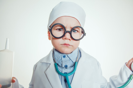 Happy little boy in doctor costum with glasses holding syringe and sthetoscope on white background.