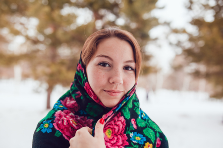 handkerchief: Russian beauty woman with red hair and freckles in the national scarf stands on a background of trees.