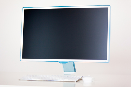 Desktop computer with wireless keyboard and mouse on white background.