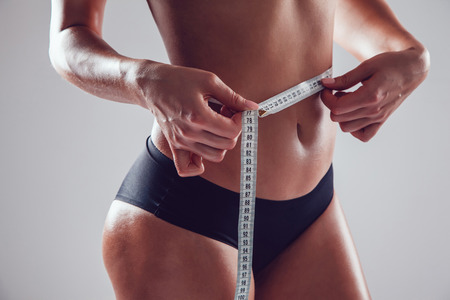 cintura: Athletic slim woman measuring her waist by measure tape on white background