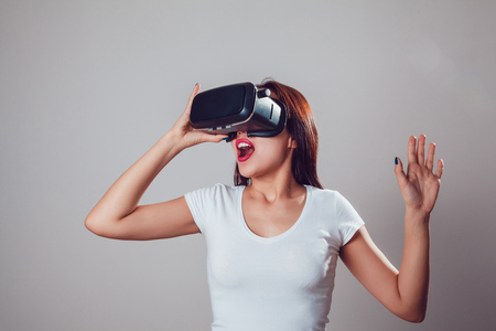 Attractive and happy woman using virtual reality goggles on grey background. VR headset.
