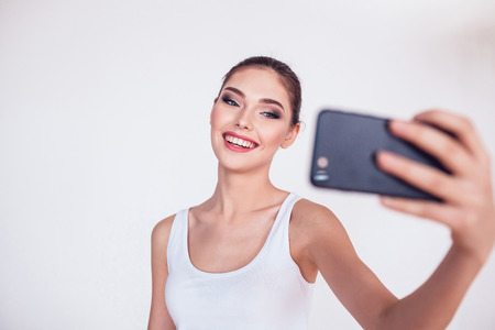 Beautiful brunette girl with makeup make selfie on white background.