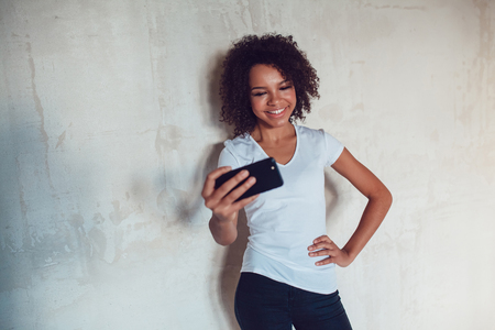 style advice: Beautiful smiling african girl make selfie on grey background Stock Photo