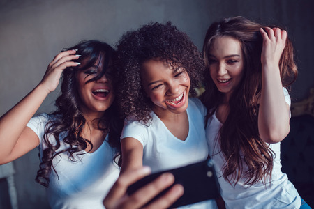 afro hairdo: Three beautyful smiling girls in white t-shirt grimace and make selfie using smartphone. Stock Photo