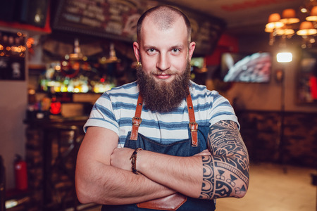 Bearded barman with tattoos wearing an apron standing at the bar with her hands folded. Stock Photo