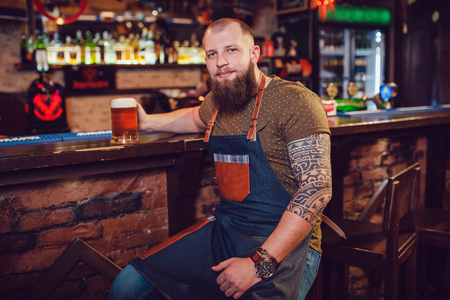 near beer: Bearded barman with tattoos wearing an apron sitting near the bar and holding a glass of beer Stock Photo