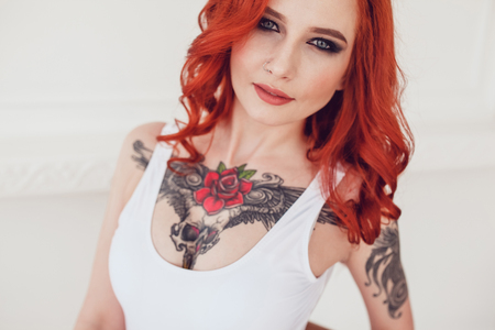 Portrait of a beautiful sexy girl with red hair and a tattoo. Woman with make-up and curls. Фото со стока