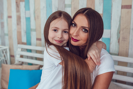 Mom and daughter with beautiful long hair are sitting in embrace. Reklamní fotografie