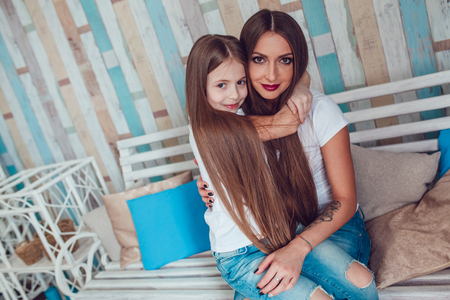 Mom and daughter with beautiful long hair are sitting in embrace. Stock Photo