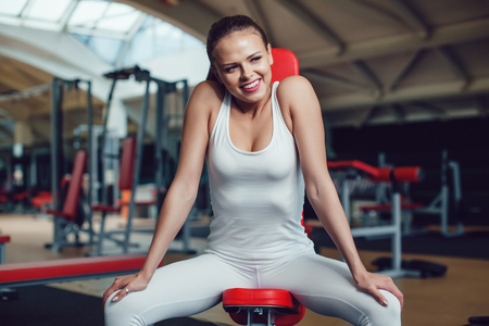 Beautiful girl sitting in the gym dressed blank white tank-top and tights. Stock Photo