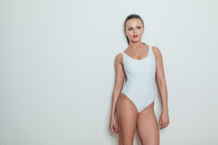 Beautiful sexy girl with tattoo in white bodysuit standing on a white background. Mock up. 版權商用圖片