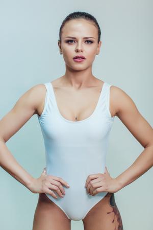 白いボディー スーツ ホワイト バック グラウンドの上に立っての入れ墨を持つ美しいセクシーな少女。モックアップを作成します。 写真素材