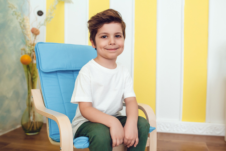 Little smiling boy in white t-shirt sitting on a baby chair. Mock up. Stock Photo