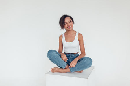 Beautiful african girl in white tops sitting on white background.