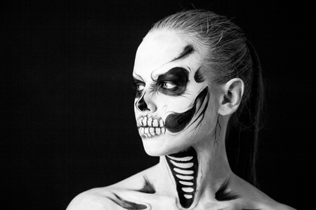 Girl with creative halloween face art on black background. Stock Photo