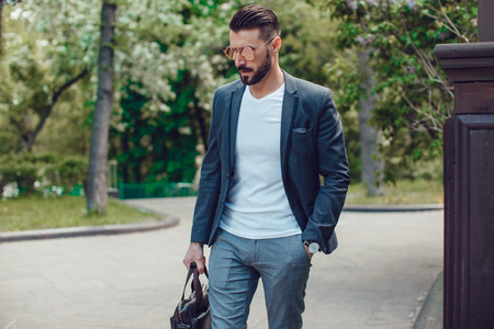 Stylish man with a beard and in sunglasses standing in the park.