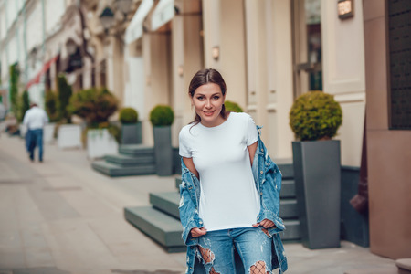Attractive girl in a jeans jacket and white t-shirt walking along the street. Mock-up.