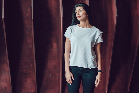 Attractive brunette woman in a white t-shirt stands on a dark wooden wall background. Mock-up.