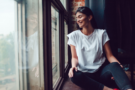 Attractive brunette in a white t-shirt sits near a window. Mock-up. Banco de Imagens - 80525347