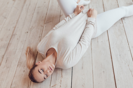 sex appeal: Sexy blonde woman in a grey sweatshirt lies on the wooden floor. Stock Photo